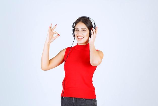 Dj in camicia rossa che indossa le cuffie e si gode la musica.