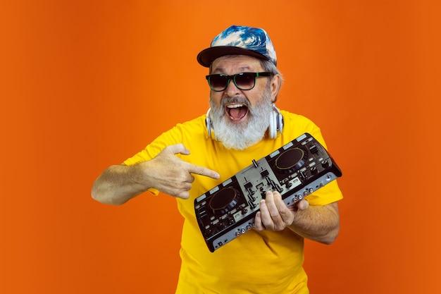 Dj 세트. 주황색 스튜디오 배경에 격리된 장치, 가제트를 사용하는 수석 힙스터 남자의 초상화. 기술 및 즐거운 노인 라이프 스타일 개념입니다. 트렌디한 컬러, 영원한 젊음. 귀하의 광고에 대 한 copyspace입니다.