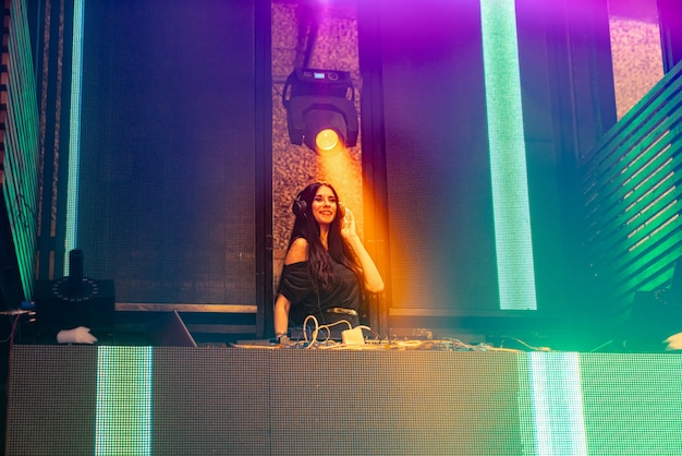 Dj on stage in disco night club mixing techno music beat