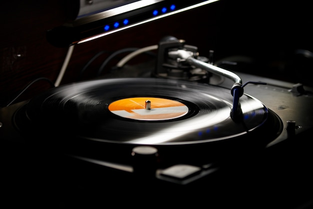 Dj turntables needle cartridge on black vinyl record with music. close up, focus on turntable and audio disc record