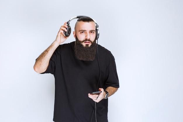 Dj con la barba che tira fuori le cuffie per ascoltare la voce esterna.