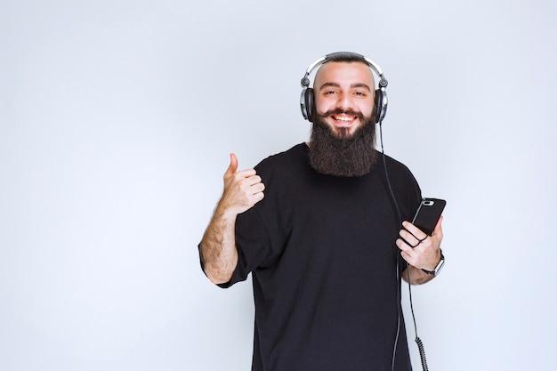 Dj с бородой в наушниках слушает плейлист на своем телефоне.