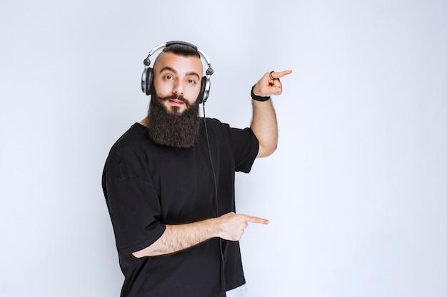 Dj с бородой в наушниках, указывая на правую сторону.