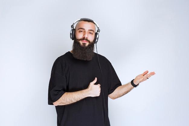 헤드폰을 착용하고 오른쪽을 가리키는 수염을 가진 dj.