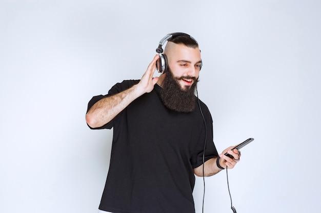 ヘッドホンをつけて、スマートフォンでプレイリストから音楽を設定しているひげを生やしたdj。