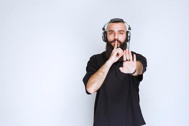 Dj con la barba che indossa le cuffie e chiede silenzio.