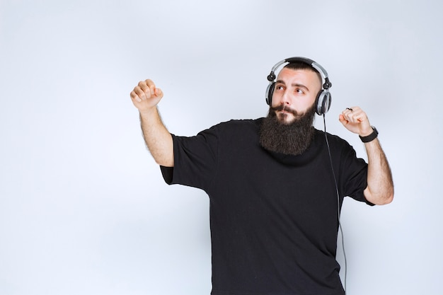 헤드폰을 쓰고 춤을 추고 활동적인 느낌을주는 수염을 가진 dj.
