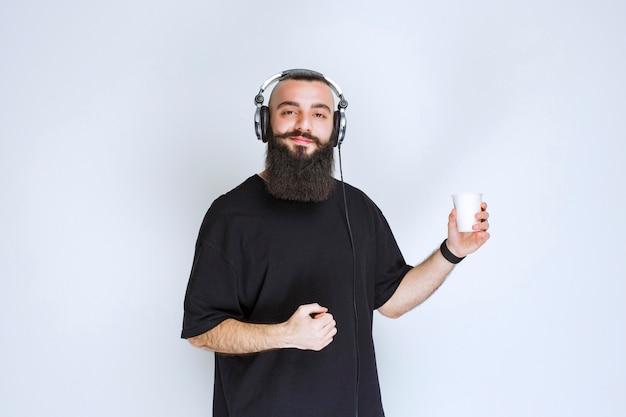 Dj con la barba che indossa le cuffie ballando e sentendosi attivo.