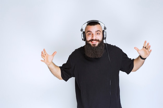 Dj with beard wearing headphones dancing and feeling active.