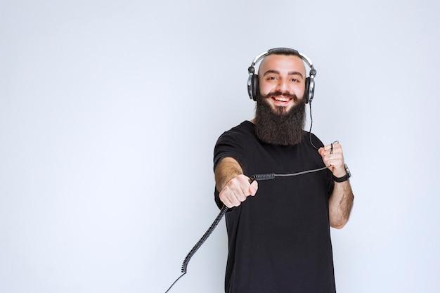 Dj con la barba che indossa le cuffie e tiene il cavo.