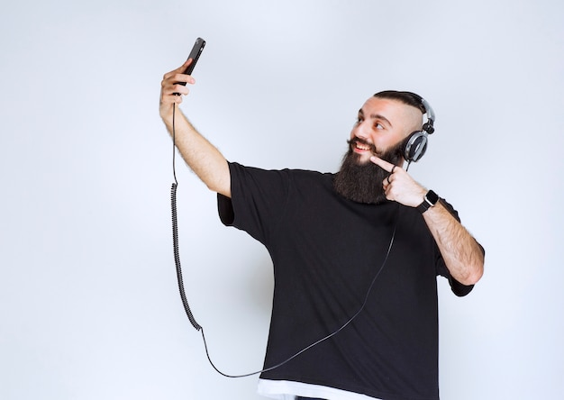 Dj with beard wearing headphones opening smartphone camera and taking his selfie.