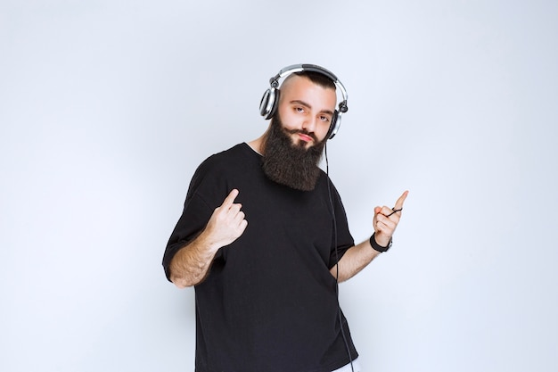 Dj with beard wearing headphones and pointing up.