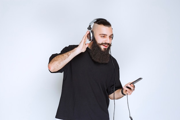 Dj with beard wearing headphones and setting music from his playlist at his smartphone.