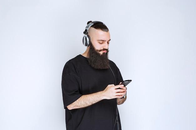 Dj con la barba che indossa le cuffie e imposta la musica dalla sua playlist sul suo smartphone.