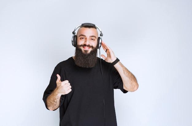 Dj con la barba che indossa le cuffie e mostra il segno positivo della mano.