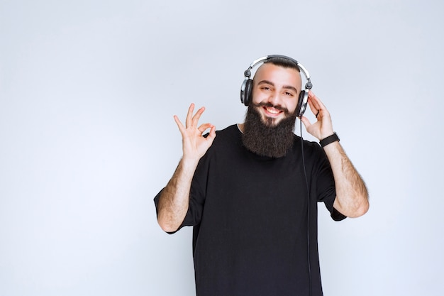 Dj with beard wearing headphones and showing positive hand sign.