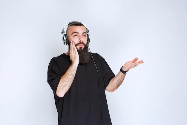Dj con la barba che indossa le cuffie, mostra il lato destro e rimane sorpreso.