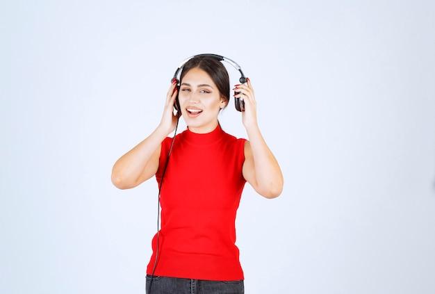Dj con le cuffie che tirano fuori un orecchio per sentire bene.