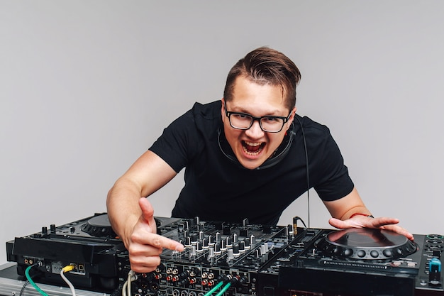 Dj with a mixer works on a gray background