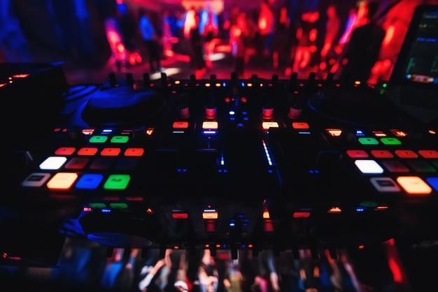 パーティーで音楽をミキシングするためのコントロールとボタンを備えたナイトクラブのミキサーdj