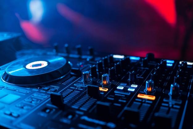 ミキサーdjがナイトクラブのパーティーでディスクを再生し、レベルとボリュームのクローズアップから音楽を再生します