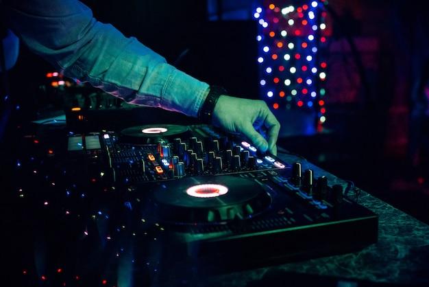 Dj играет электронную музыку в ночном клубе на вечеринке