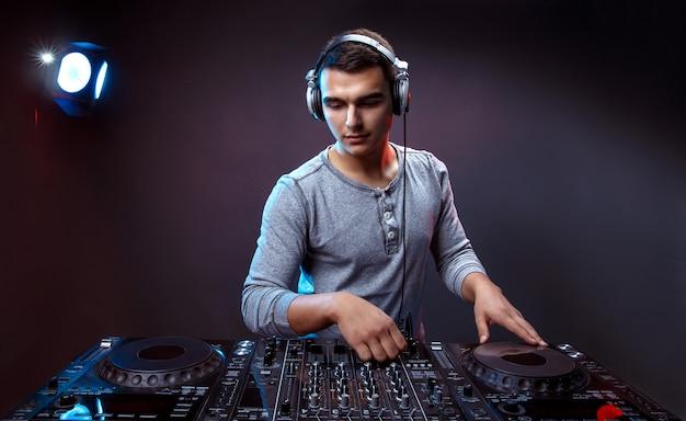 若い男がスタジオでdjのミキサーで音楽を再生