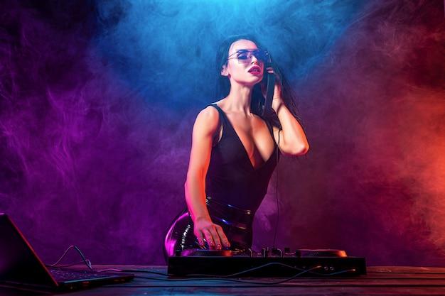 音楽を演奏するサングラスを持つ若いセクシーなdj