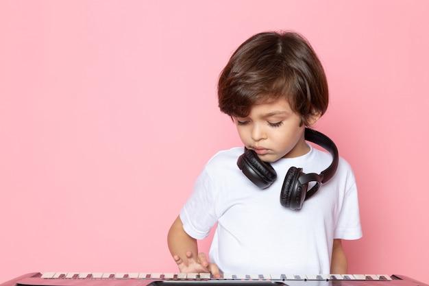Dj мальчик в белой футболке в черных наушниках и играет на пианино