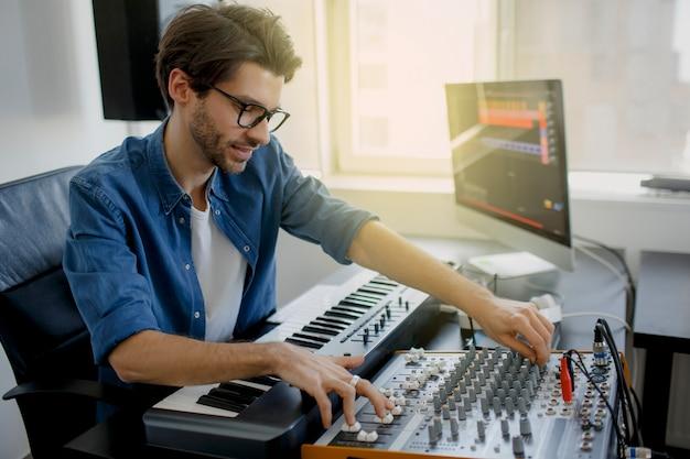 音楽プロデューサーは、レコーディングスタジオでシンセサイザーキーボードとコンピューターで曲を作曲しています。男はレコーディングスタジオでサウンドミキサーに取り組んでいる、またはdjは放送スタジオで働いている