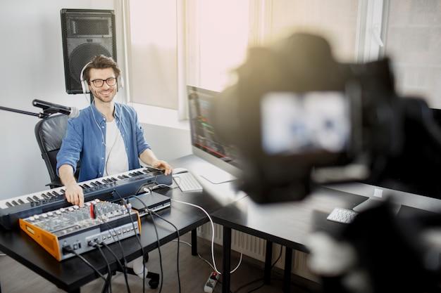 ライブビデオブロガーは、音楽トラックをライブにする方法を教えています。ソーシャルネットワークまたはストリームのビデオ。放送スタジオのdj。音楽プロデューサーがレコーディングスタジオで曲を作曲しています。