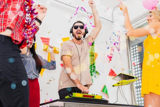 ターンテーブルのdj。白い部屋のパーティーで応援しながら紙吹雪を投げることを祝う若い人々のグループ。