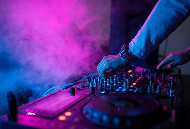Djがナイトクラブのサウンドミキサーで音楽を演奏する