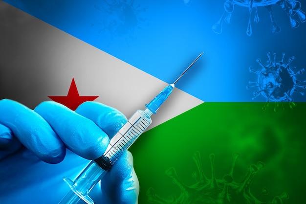 지부티 코비드19 예방 접종 캠페인 파란색 고무 장갑을 끼고 깃발 앞에 주사기를 들고 있습니다
