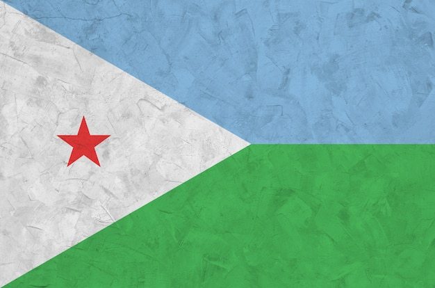 Djibouti flag depicted in bright paint colors on old relief plastering wall.