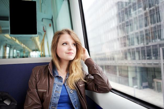 若い女性はコペンハーゲンdkで電車で旅行します。