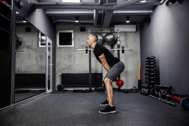 검은 티셔츠를 입은 스포츠웨어를 입은 dman은 다리를 벌리고 서서 체육관에서 양팔로 주전자 벨을 들어 올립니다.