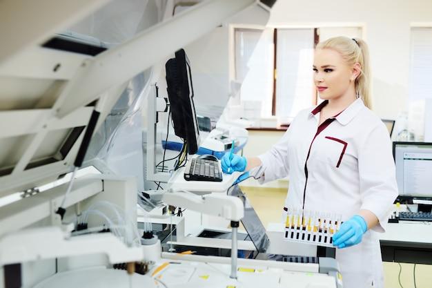 医療微生物研究所の分析装置の近くの女性科学者。分析用機器、dna、pcr