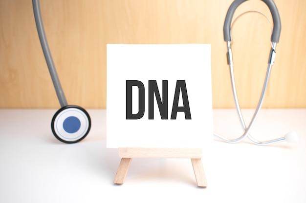 Знак днк на небольшой деревянной доске на мольберте с медицинским стетоскопом