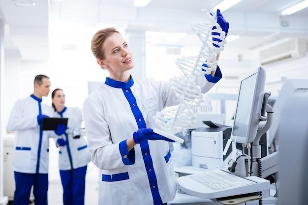 Dna 구조. dna 모델을 들고 실험실 코트를 입고 연구하는 아름다운 반사 여성 연구원