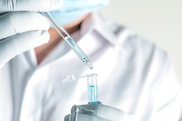 Dna分子から抽出された青を分析するために実験室で働いている科学者を閉じます。