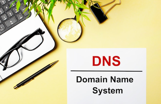 Dns domain name system is written in red on a white piece of paper on a light yellow surface next to a laptop, pen, magnifying glass, glasses and a green plant