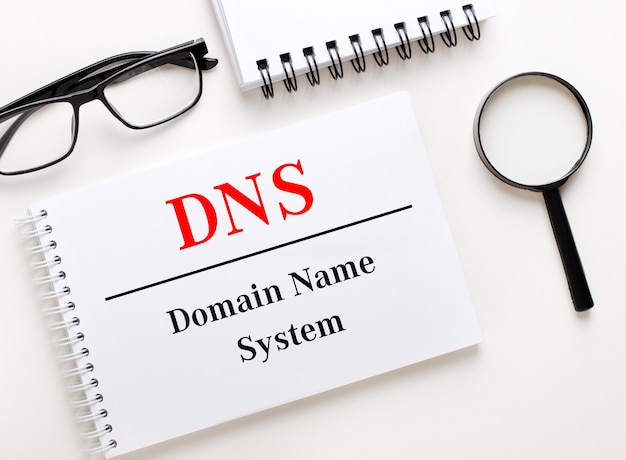 Dns domain name system is written in a white notebook on a light surface near the notebook, blackframed glasses and a magnifying glass