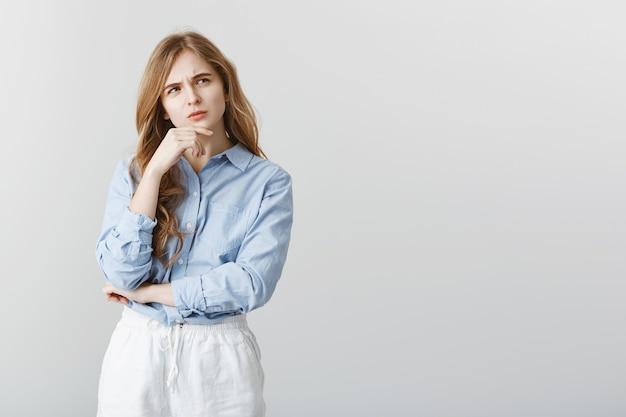 Мне правда нужно идти на встречу. портрет сосредоточенной серьезной кавказской девушки со светлыми волосами, касающейся подбородка и хмурящейся, смотрящей в сторону, думая или вспоминая важную информацию