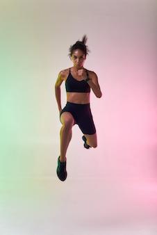 スポーツウェアのジャンプで完璧な体を持つ若いアスリート女性の全長を行います