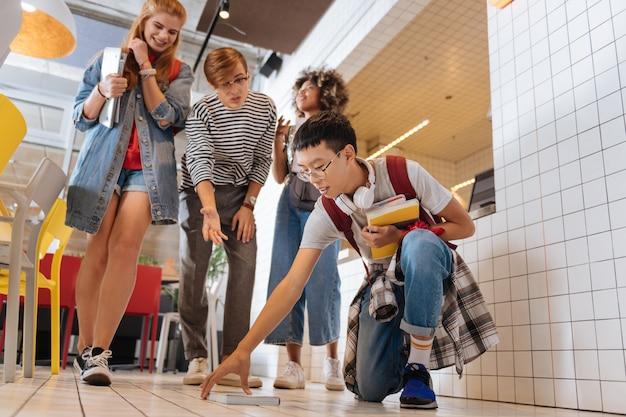 Сделай это быстро. довольные ученики, стоящие вместе, дразнят своего товарища по группе