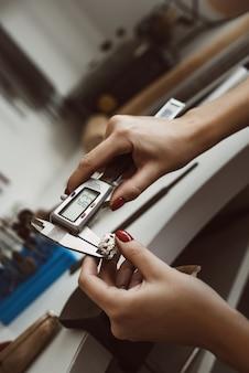Сделайте это прямо крупным планом фото рук женщин-ювелиров, измеряющих кольцо с помощью инструмента
