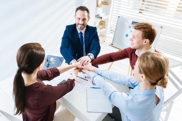 やれ。ニヤリとテーブルで作業しながら手を合わせている陽気な陽気な4人の同僚の上面図