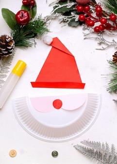 Сделай сам на рождество. прохождение. шаг второй наклейте листочки бумаги на половину пластиковой тарелки.