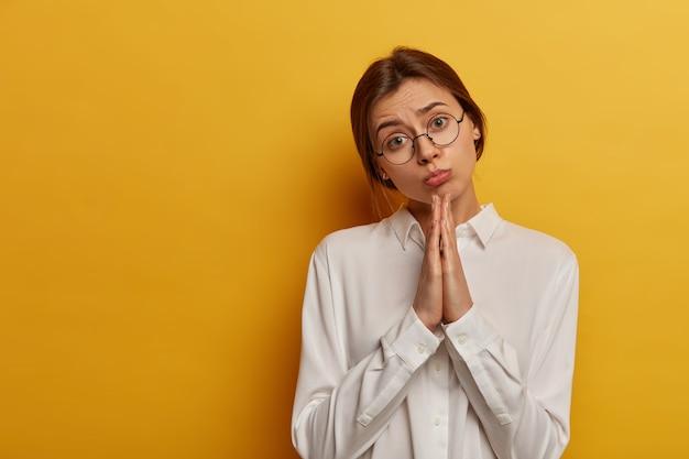 한 번 더 부탁드립니다! 젊은 매력적인 여자는 슬픈 얼굴을 가지고,기도 제스처에 두 손바닥을 보유하고, 친구에게 도움을 청하고, 흰색 셔츠를 입는다.